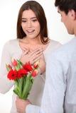 Mujer que es sorprendida con el manojo de flores Imagenes de archivo