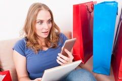 Mujer que es sorprendida sosteniendo smartphone y la tableta Imágenes de archivo libres de regalías