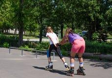 Mujer que es tirada adelante por un patinador joven del rodillo Fotografía de archivo