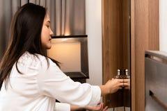 Mujer que escoge una botella de perfume del gabinete de almacenamiento de madera imagen de archivo
