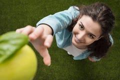 Mujer que escoge una manzana Foto de archivo libre de regalías