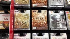 Mujer que escoge veinticinco dólares de carte cadeaux de la visa almacen de video