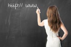 Mujer que escribe el URL en la pizarra Fotografía de archivo libre de regalías