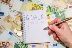 Mujer que escribe la lista de la resolución de los Años Nuevos contra billete de banco euro Imagen de archivo