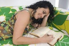 mujer que escribe un cuaderno que se sienta en una butaca Fotos de archivo libres de regalías