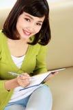 Mujer que escribe un libro mientras que se sienta en el sofá Imágenes de archivo libres de regalías