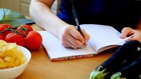 Mujer que escribe un recibo en un cuaderno Vehículos en el vector almacen de metraje de vídeo