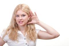 Mujer que escucha detras de las puertas con la mano detrás de su oído Foto de archivo
