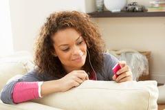 Mujer que escucha el jugador MP3 en los auriculares Fotografía de archivo libre de regalías