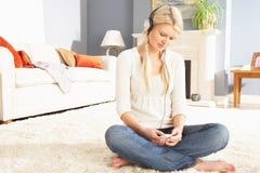 Mujer que escucha el jugador MP3 que se sienta en la manta Imagen de archivo libre de regalías
