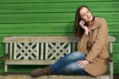 Mujer que escucha en el teléfono al aire libre Imagenes de archivo
