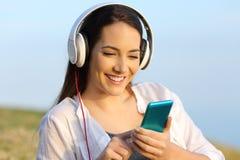 Mujer que escucha la música al aire libre en la hierba Imágenes de archivo libres de regalías