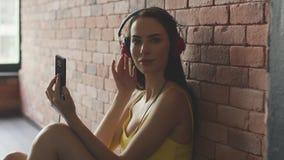 Mujer que escucha la música cerca de la pared metrajes