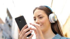 Mujer que escucha la música que comprueba canciones metrajes