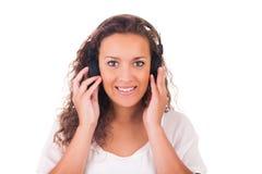 Mujer que escucha la música con los auriculares foto de archivo