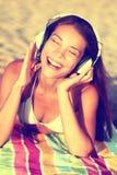 Mujer que escucha la música con los auriculares en la playa Fotografía de archivo