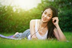 Mujer que escucha la música con los auriculares y que pone en una hierba f Fotografía de archivo libre de regalías
