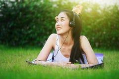 Mujer que escucha la música con los auriculares y que pone en una hierba f Imagen de archivo