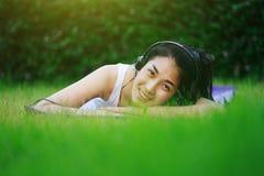 Mujer que escucha la música con los auriculares y que pone en una hierba f Imagenes de archivo