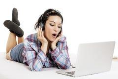 Mujer que escucha la música con los auriculares y que usa el lapt del ordenador Fotografía de archivo libre de regalías