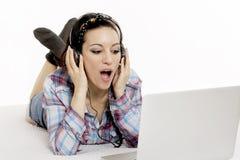 Mujer que escucha la música con los auriculares y que usa el lapt del ordenador Imagen de archivo libre de regalías