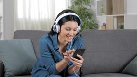 Mujer que escucha la música del teléfono celular almacen de video
