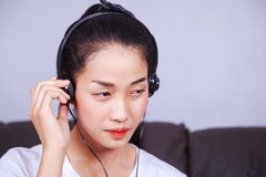Mujer que escucha la música en auriculares en el sofá en casa Imágenes de archivo libres de regalías