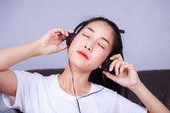 Mujer que escucha la música en auriculares en el sofá en casa Imagenes de archivo