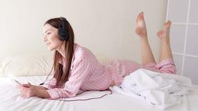 Mujer que escucha la música en auriculares grandes con la mentira del teléfono metrajes