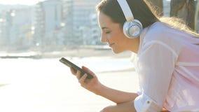 Mujer que escucha la m?sica en la costa almacen de metraje de vídeo