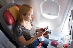 Mujer que escucha la música en el teléfono elegante en el aeroplano comercial de los pasajeros durante vuelo Fotografía de archivo libre de regalías