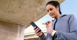 Mujer que escucha la música en el teléfono móvil mientras que activa 4k almacen de metraje de vídeo