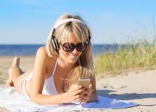 Mujer que escucha la música en los auriculares en la playa Imagen de archivo libre de regalías