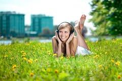 Mujer que escucha la música en los auriculares o Imagenes de archivo