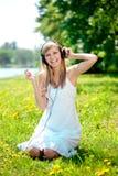 Mujer que escucha la música en los auriculares o Fotos de archivo