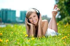 Mujer que escucha la música en los auriculares o Imagen de archivo
