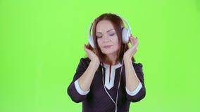 Mujer que escucha la música en los auriculares Pantalla verde almacen de metraje de vídeo