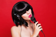 Mujer que escucha la música en los auriculares que gozan de a Imagenes de archivo