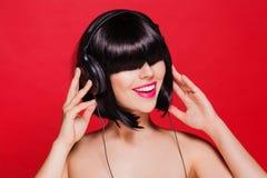 Mujer que escucha la música en los auriculares que gozan de a Fotos de archivo
