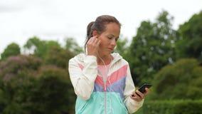 Mujer que escucha la música en smartphone en el parque almacen de video