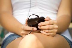Mujer que escucha la música en su teléfono Imagen de archivo