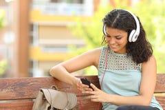 Mujer que escucha la música en un parque Foto de archivo