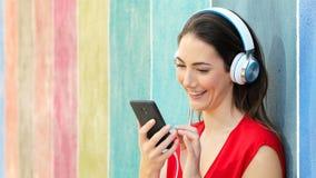 Mujer que escucha la música en una pared colorida