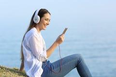 Mujer que escucha la música que se relaja en la playa Imagenes de archivo