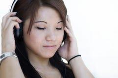 Mujer que escucha la música a través de los teléfonos principales Foto de archivo libre de regalías