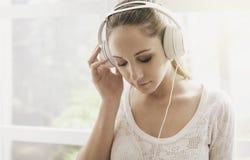 Mujer que escucha la m?sica en casa imagen de archivo libre de regalías