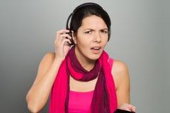 Mujer que escucha la música que lucha para oír Fotos de archivo