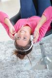Mujer que escucha los auriculares mientras que en silla Imágenes de archivo libres de regalías