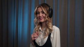 Mujer que escucha su música en los auriculares y que baila un poco metrajes
