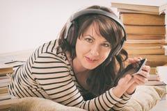 Mujer que escucha un audiolibro fotografía de archivo